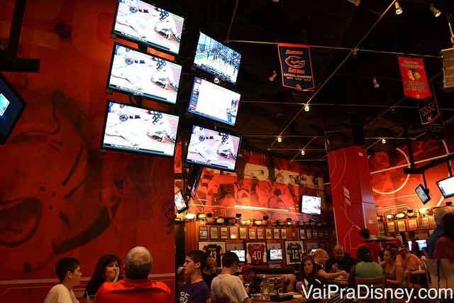 Foto do interior do bar, com muitas telas passando esportes