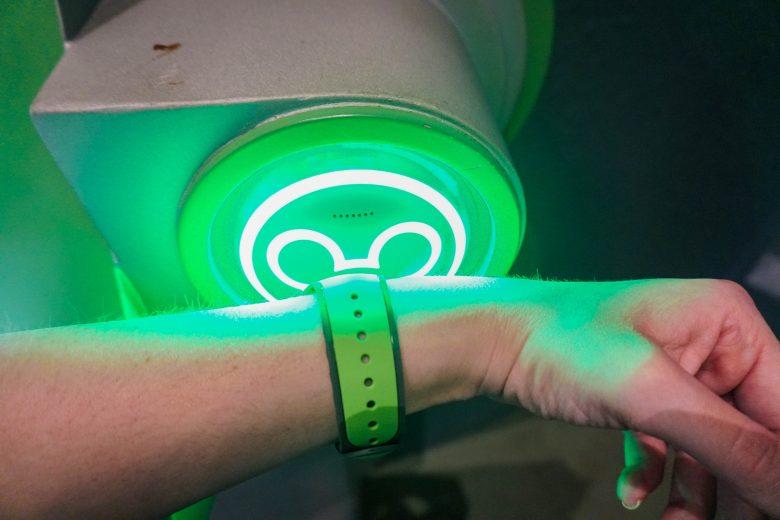 Foto de uma mão com uma MagicBand verde sendo escaneada em uma atração da Disney, no totem de Mickey que fica verde para autorizar a entrada