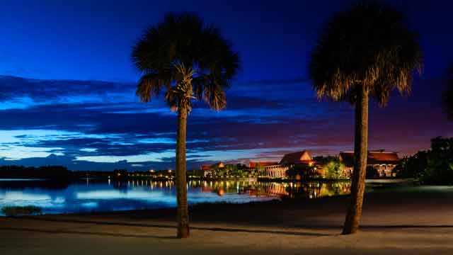 Foto de divulgação da Disney do Disney's Polynesian Resort, visto de longe, todo iluminado com a praia e as palmeiras ao seu redor.