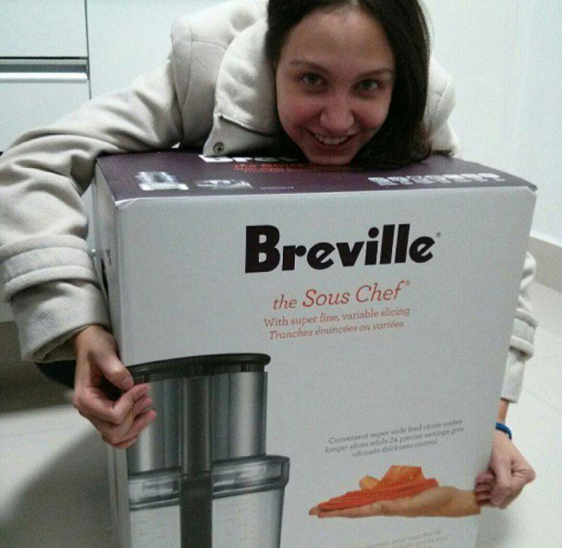 Foto da Renata abraçada a uma caixa de um utensílio de cozinha