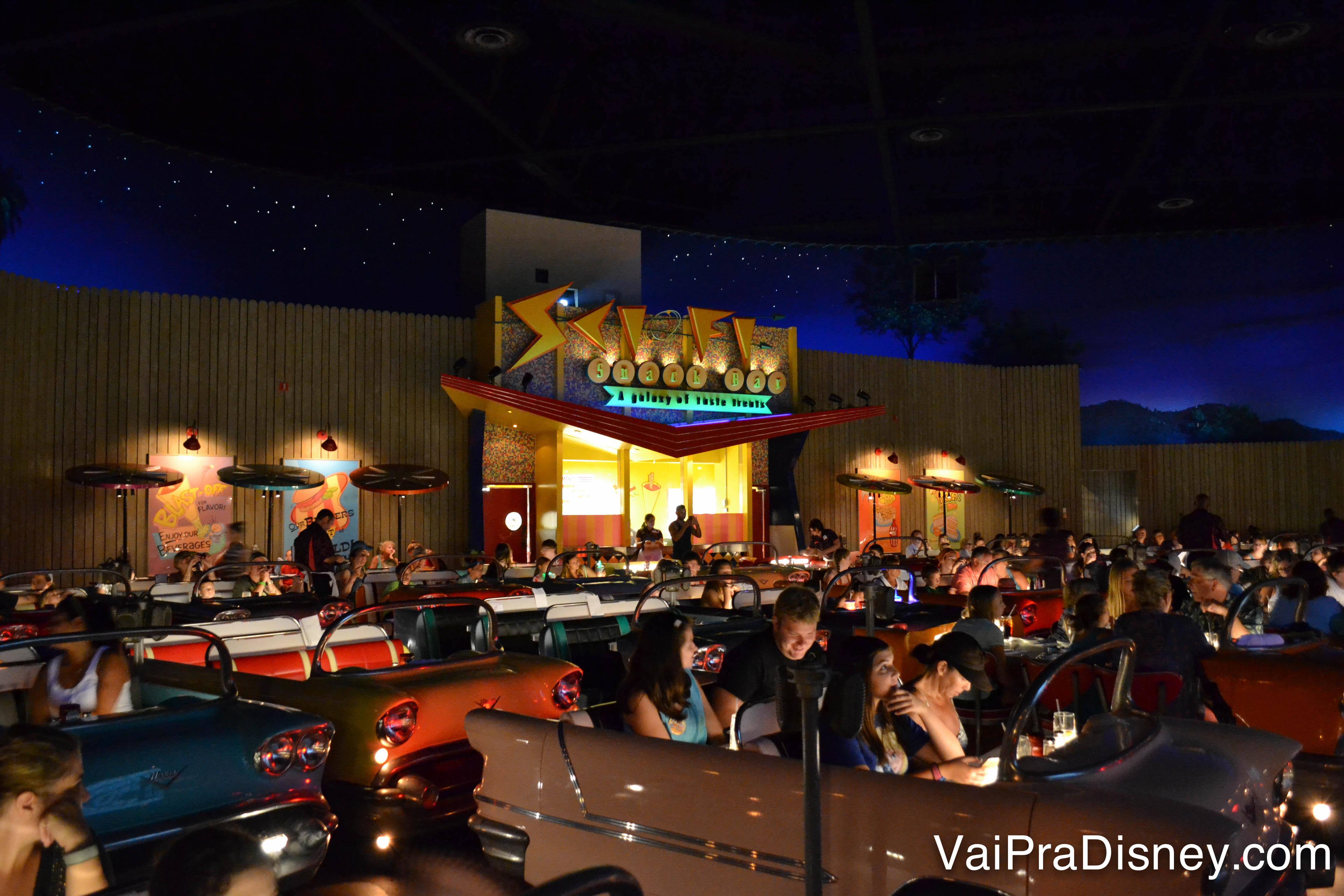 Foto do Sci-Fi Dine in Theater, o restaurante drive-in da Disney, com diversos carros antigos estacionados na frente e os visitantes dentro.