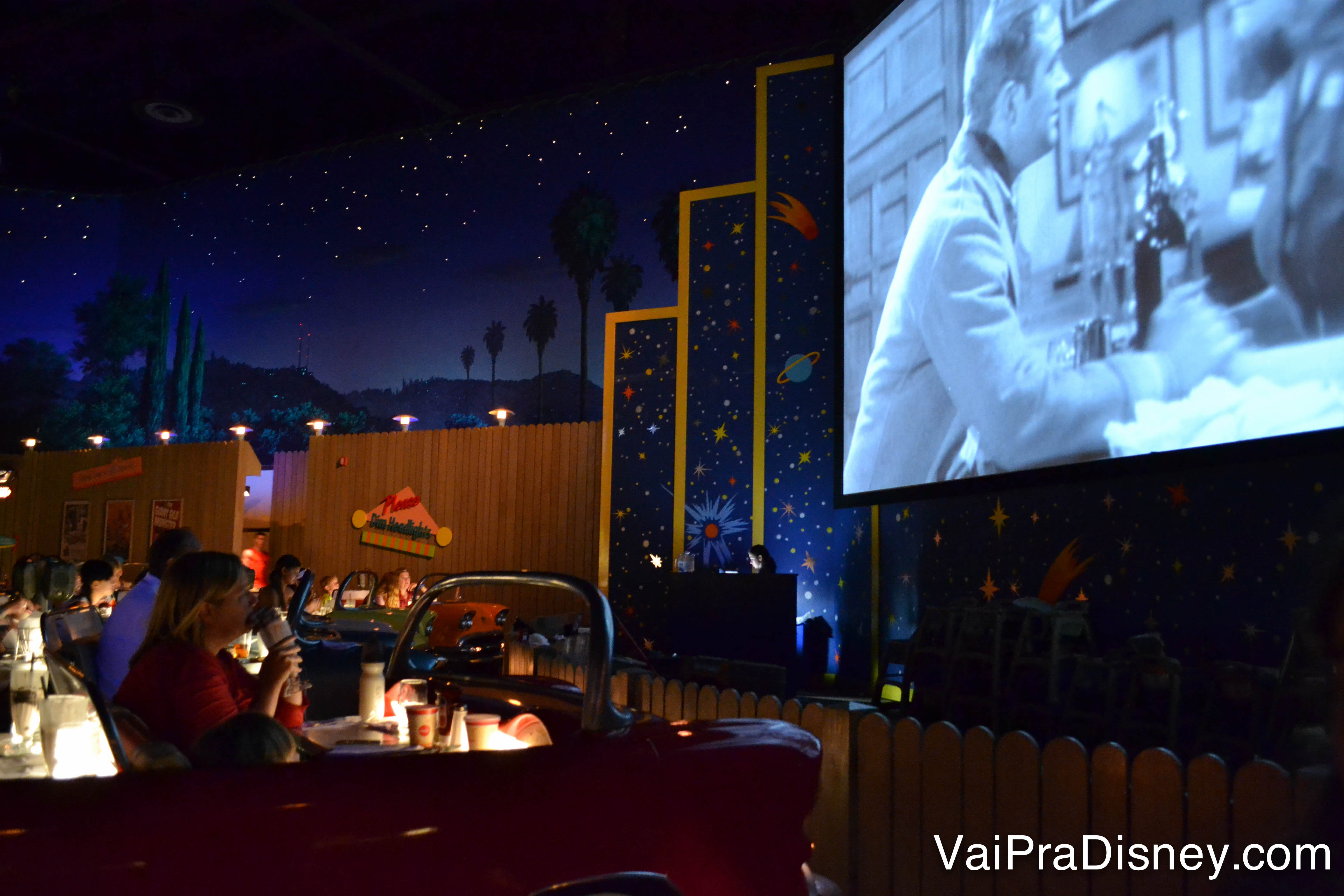 Foto do restaurante, com os carros antigos e a tela passando um filme antigo. O ambiente é escuro para imitar um drive-in à noite
