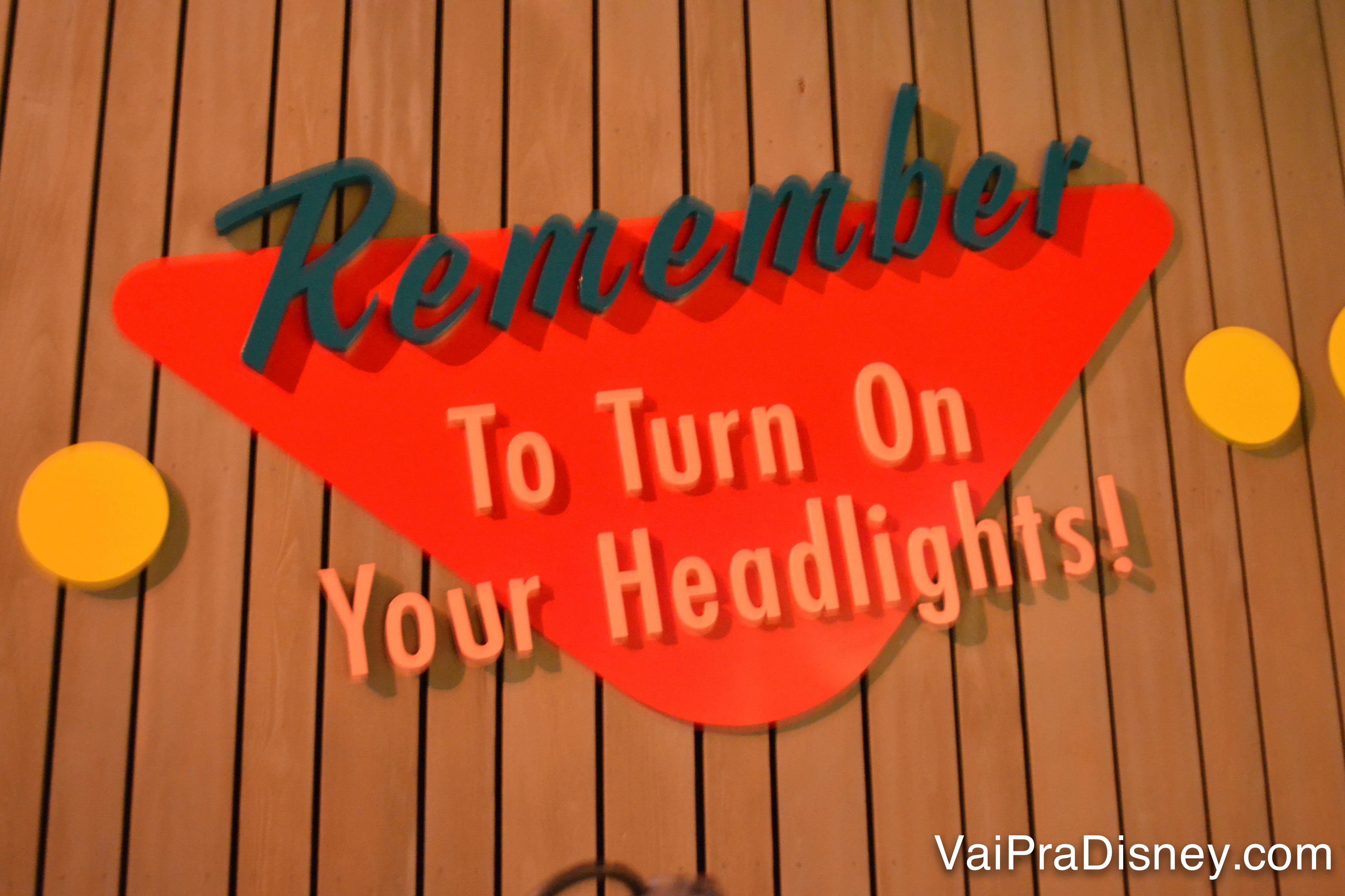 """Placa imitando um aviso de drive-in antigo, que diz """"Remember to turn on your headlights"""""""