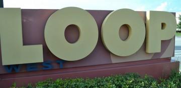 Foto da placa na entrada do The Loop, um dos principais complexos de compras de Orlando e região