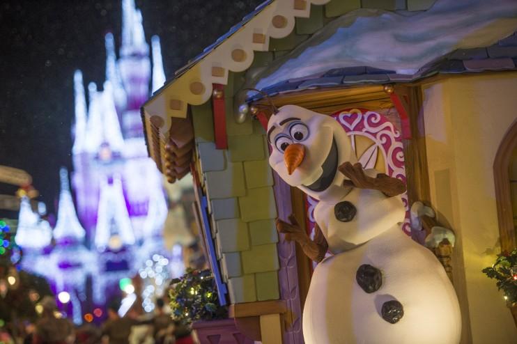 Não aguento a fofura do Olaf na parada de Natal, gente! Foto do Olaf durante a parada de Natal do Magic Kingdom, com o castelo da Cinderela iluminado ao fundo.