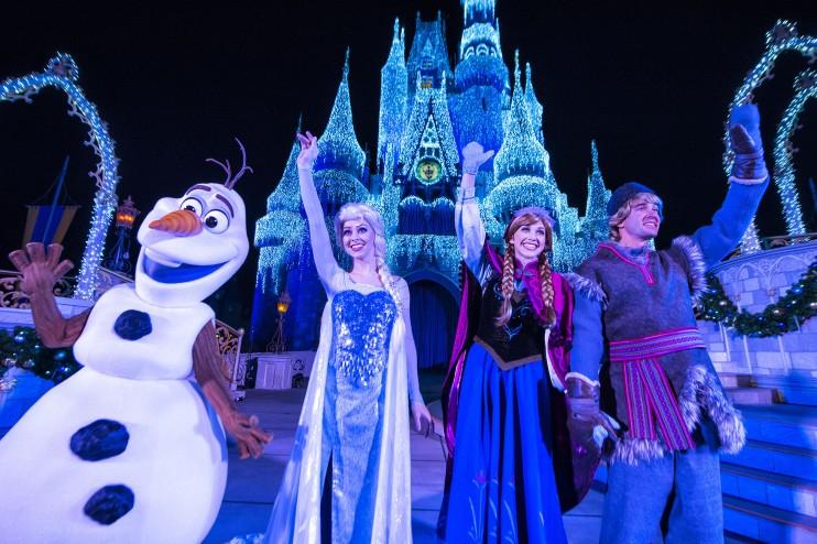 Personagens de Frozen iluminando o castelo no Frozen Holiday Wish. Foto da rainha Elsa, princesa Anna, Olaf e Kristoff em frente ao castelo da Cinderela no Magic Kingdom, iluminado em tons de azul contra o céu escuro.