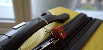 Foto de uma mala amarela com um cadeado no zíper, um recurso para evitar roubos e furtos na viagem