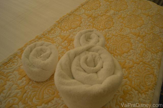 Pequenos detalhes como esse estão sempre espalhados pelo quarto te lembrando que você está dentro da Disney. Foto de toalhas enroladas em formato de Mickey sobre a cama do hotel.