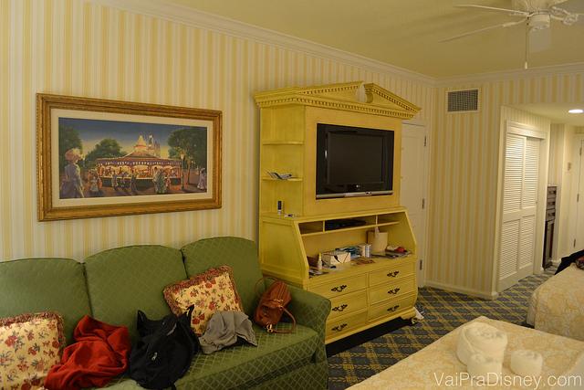 Não repara a bagunça no nosso sofá, tá? ;) Foto do quarto do hotel, mostrando o móvel de TV amarelo e um sofá verde com mochilas em cima.