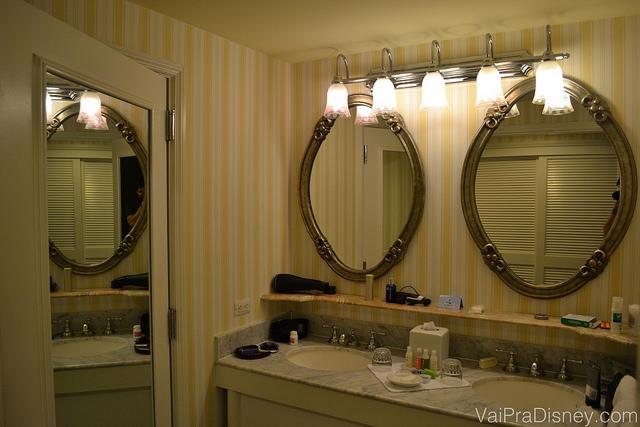 Essa área das pias é bem espaçosa, mas o resto do banheiro em si é bem parecido com o padrão dos hotéis econômicos da Disney. Foto do banheiro do hotel, com dois espelhos, pia dupla e papel de parede listrado amarelo e branco