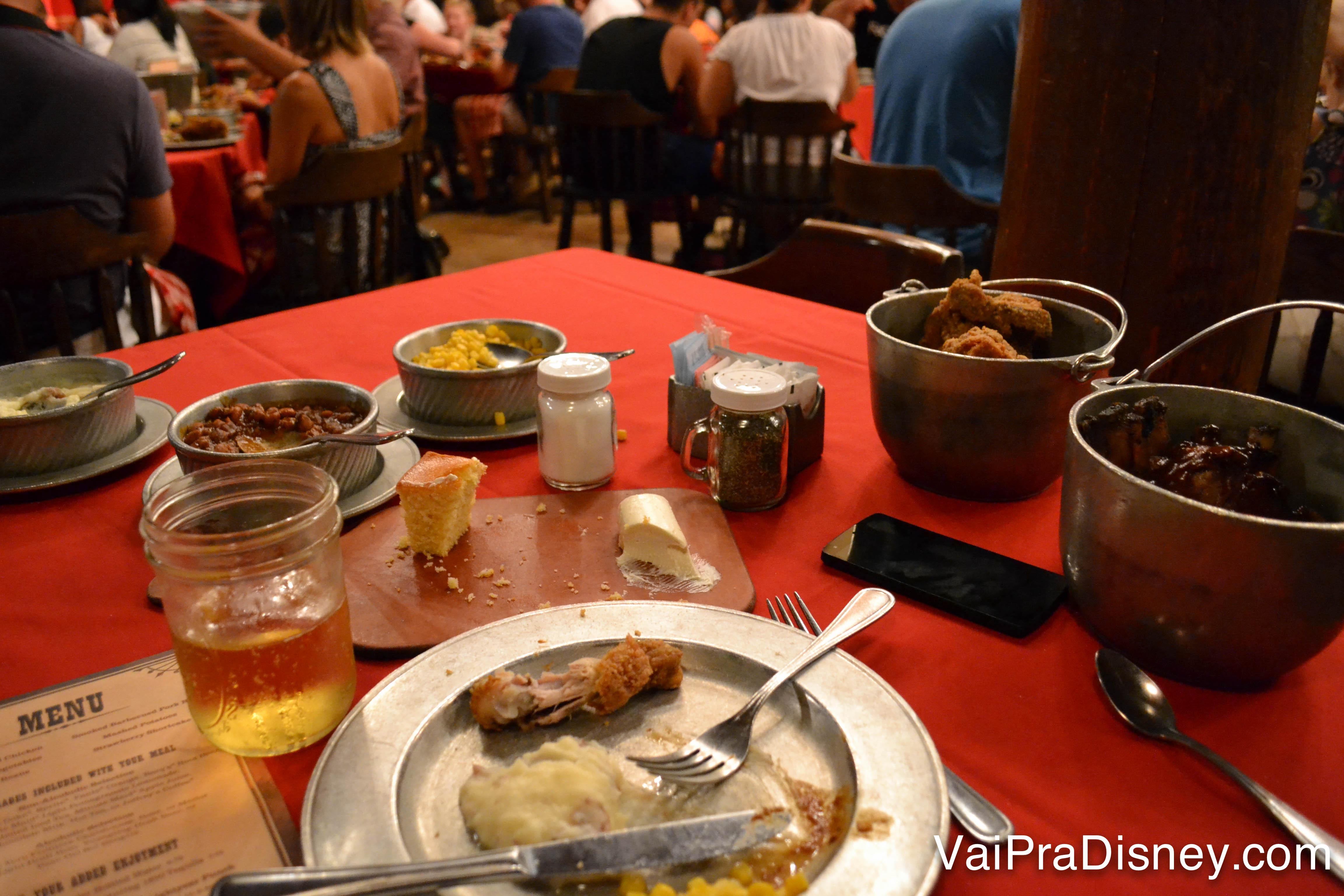 A mesa cheia de pratos, copos e ainda algumas porções de comida no fim da noite do Hoop-Dee-Doo Musical Revue