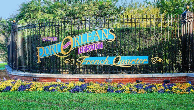 Placa do hotel Port Orleans French Quarter, com grama e flores abaixo do portão