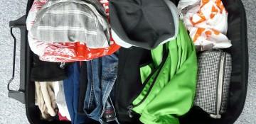 Foto do interior de uma mala de viagem, com diversas roupas e uma nécessaire