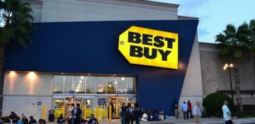 Foto da fachada da loja Best Buy que fica em frente ao shopping Mall at Millenia. Uma das mais lotadas de Orlando. Ela é pintada de azul e sua placa é amarela.