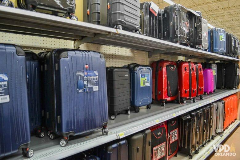 Comprar malas nos EUA geralmente vale muito a pena também! A foto mostra diversas malas em cores variadas no corredor de uma loja.