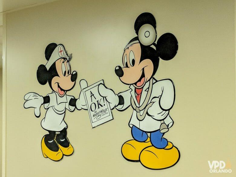 A gente espera não precisar usar, mas é sempre bom estar coberto durante a viagem e um bom seguro precisa entrar no seu pacote! Foto da central de atendimento médico da Disney, que mostra o Mickey e a Minnie com roupas de médicos.