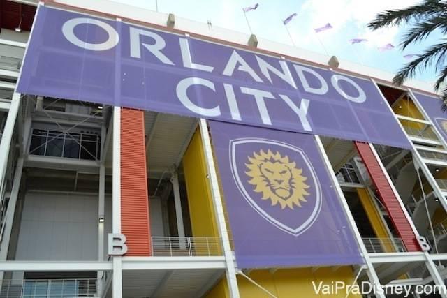Foto do lado de fora do estádio, com as cores e o brasão do Orlando City (um leão amarelo no fundo roxo)