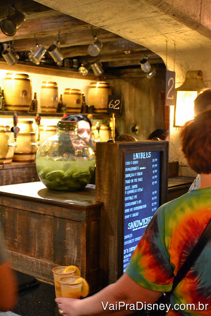 Foto do balcão onde são feitos os pedidos no Caldeirão Furado, com um cardápio digital em frente a ele e uma atendente atrás