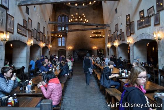 Foto do interior do Caldeirão Furado do Beco Diagonal, no Universal Studios. O ambiente é amplo, com um lustre central e mesas longas de madeira dos dois lados de um espaço vazio central.