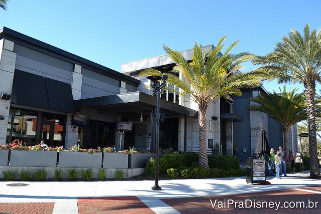 Restaurante no ICON Park. Foto da entrada do restaurante no ICON Park, com uma palmeira na frente e alguns visitantes passando