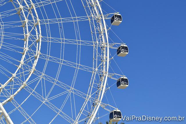 Essas são as famosas cápsulas de vidro da The Wheel. Foto da roda-gigante The Wheel mostrando metade dela, com as cápsulas de vidro onde entram os visitantes e o céu azul ao fundo.