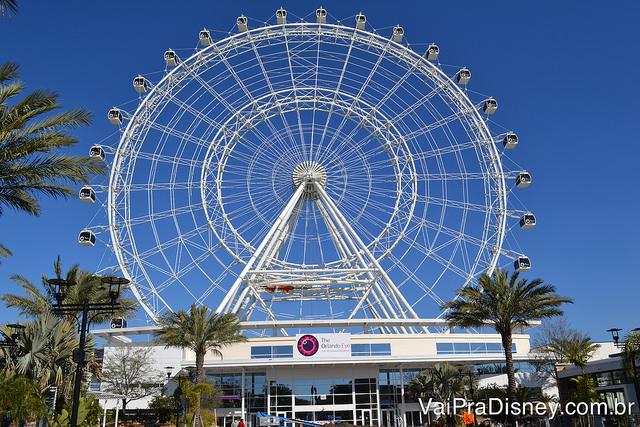 The Wheel.  Foto da roda-gigante conhecida como The Wheel, em Orlando, com o céu azul ao fundo e a entrada do ICON Park em primeiro plano.