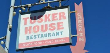 Foto da placa do restaurante Tusker House, que fica no Animal Kingdom. Ela tem fundo branco e as letras em vermelho e verde.