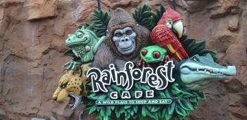 Foto da placa do Rainforest Cafe, que tem diversos animais como gorila, arara, onça e sapo.