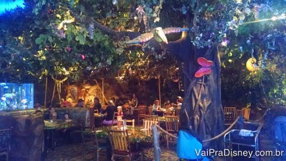 Foto do interior do Rainforest Cafe com a decoração florestal, com árvores, cipós e borboletas