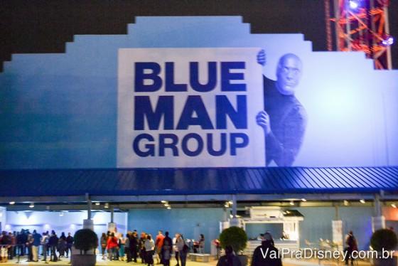 Foto da entrada do teatro do Blue Man Group em Orlando, com um dos membros espiando de trás da placa com o nome do grupo
