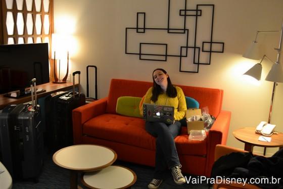 Antessala com TV tela plana. Esse sofá laranja que a Re ta sentada vira uma cama de casal.