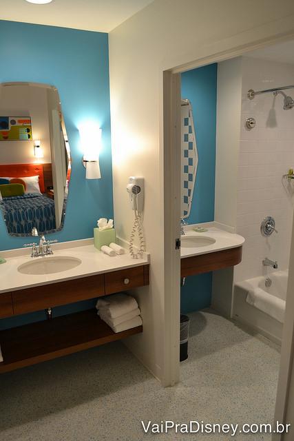 Pia central do banheiro e cabine com outra pia e chuveiro