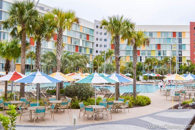 Foto da área da piscina do hotel, com guarda-sóis coloridos, assim como o próprio prédio