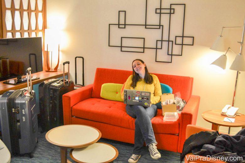 Foto da Renata na antessala da Family Suite, sentada em um sofá laranja com um notebook no colo