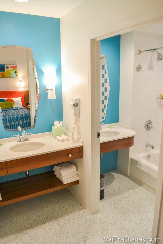 Foto do banheiro da Family Suite, com uma pia central e uma cabine com outra pia e chuveiro