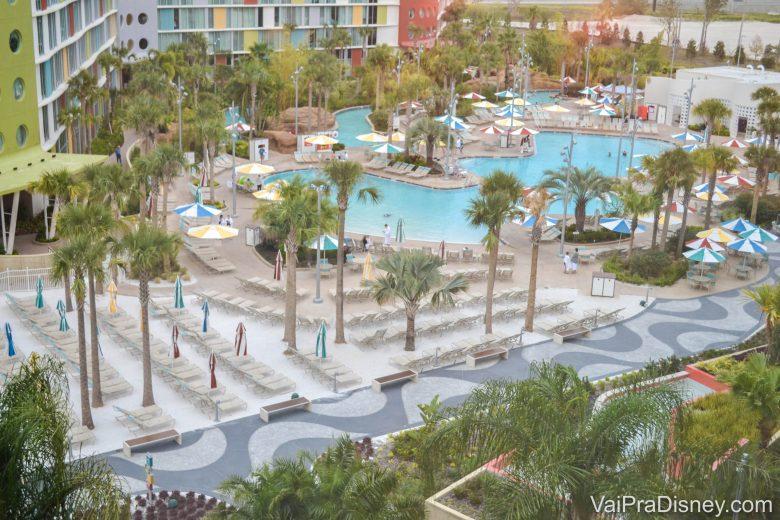Foto de uma das piscinas do Cabana Bay, vista de cima, bem grande e rodeada de palmeiras