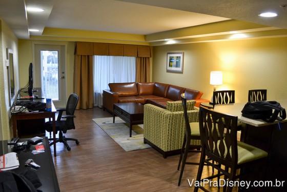 Foto da sala enorme do quarto que ficamos, chamado de Junior Suite, com um sofá grande, uma poltrona, uma mesa de jantar e um canto de escritório