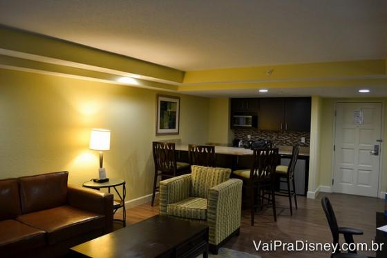 Outro ângulo da sala + cozinha do apartamento, mostrando mais a cozinha e a poltrona