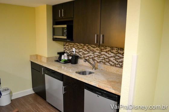Mini-cozinha do quarto, com armários, microondas, pia e cafeteira