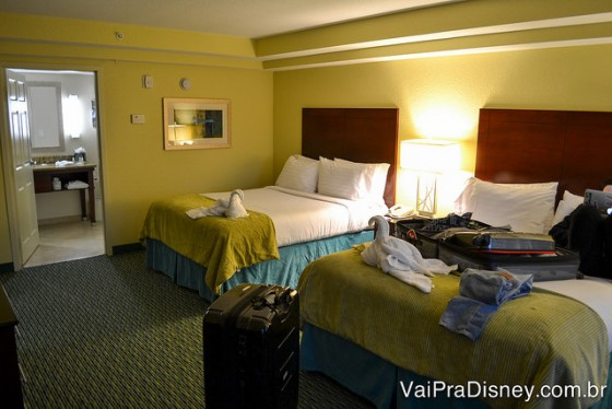 Foto do quarto, com uma das camas com a mala aberta em cima e roupas espalhadas