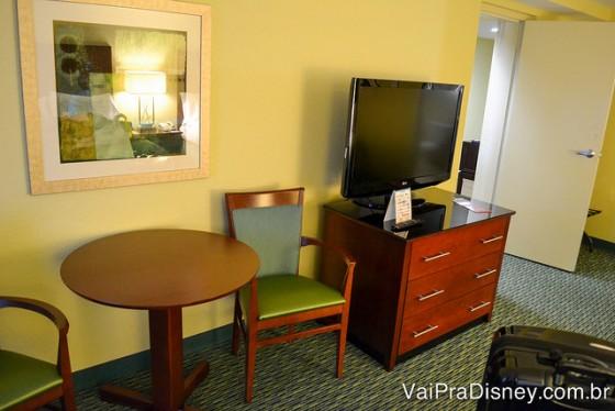 Foto da TV do quarto com uma mesa e 2 cadeiras ao lado