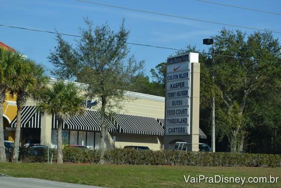 Foto da entrada do Lake Buena Vista Factory Stores, com uma placa grande com o nome das lojas presentes, algumas árvores e o céu azul ao fundo