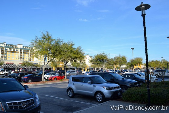 Foto do estacionamento do Lake Buena Vista Factory Stores, com diversos carros e o céu azul ao fundo