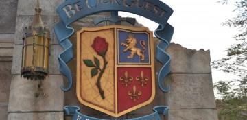 Foto da placa na entrada do restaurante Be our Guest, no Magic Kingdom. Ela imita um brasão medieval com uma rosa, um leão e espadas.