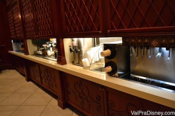 Ilha de bebidas para pegar à vontade. Foto da ilha de bebidas do restaurante, com copos e diversos tipos de refrigerante na máquina.
