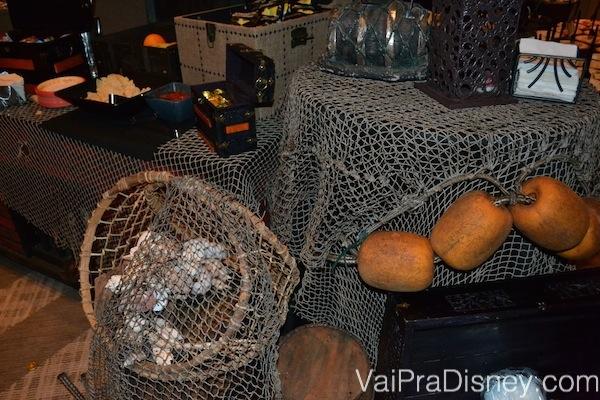 Foto dos detalhes da decoração das mesas, com redes de navio e tema pirata