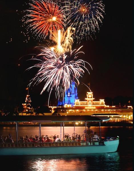 Foto dos fogos do Magic Kingdom, com o castelo e o parque iluminados ao fundo, e o  barco do Pirates & Pals Fireworks Voyage em primeiro plano