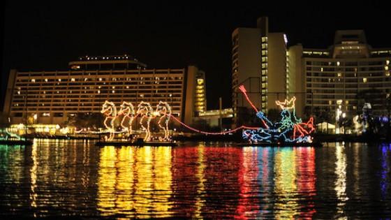 Foto do evento o Electrical Water Pageant, com barcos iluminados na água e alguns hotéis ao fundo.