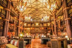 A imagem mostra o lobby do Animal Kingdom Lodge, um dos hotéis de luxo da Disney. A decoração é toda em madeira, com pilares, teto alto e lustres coloridos.