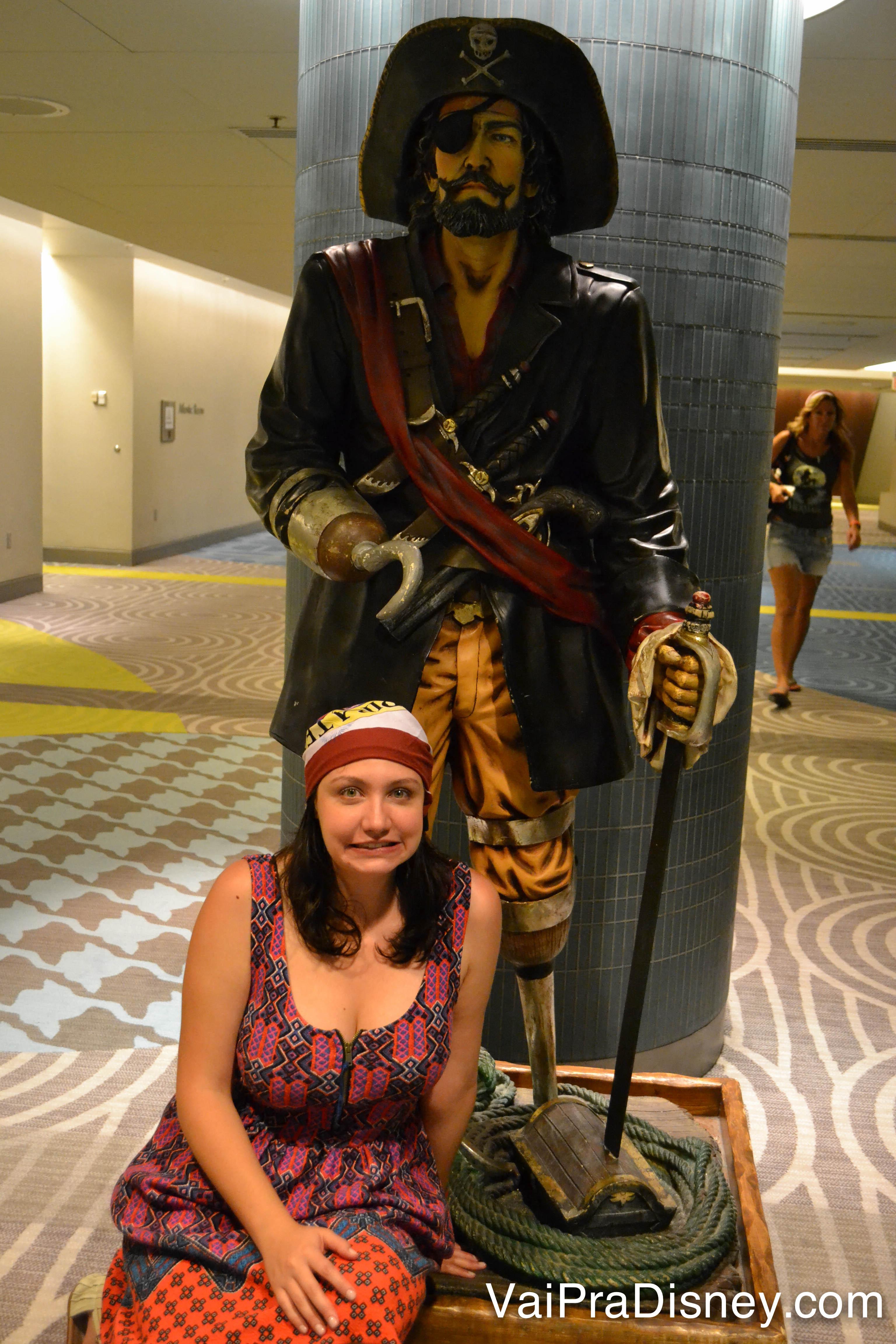 Foto da Renata de bandana pirata sentada aos pés da estátua do pirata na Pirates & Pals Fireworks Voyage